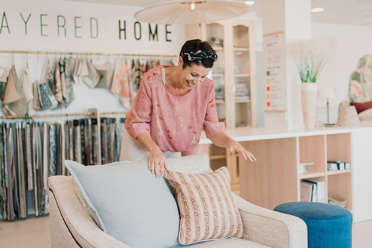 woman arranging cushions on a chair