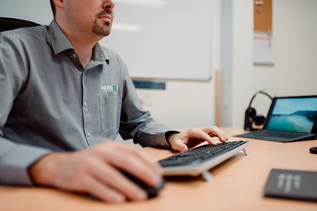 man working at a desk with a keyboard